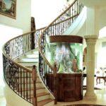 Аквариум в форме цилиндра у винтажной лестницы
